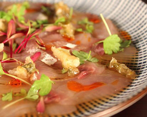 Kingfish belly carpaccio with chili oil and a sweet ginger and mirin sauce, topped with tempura jalapeno